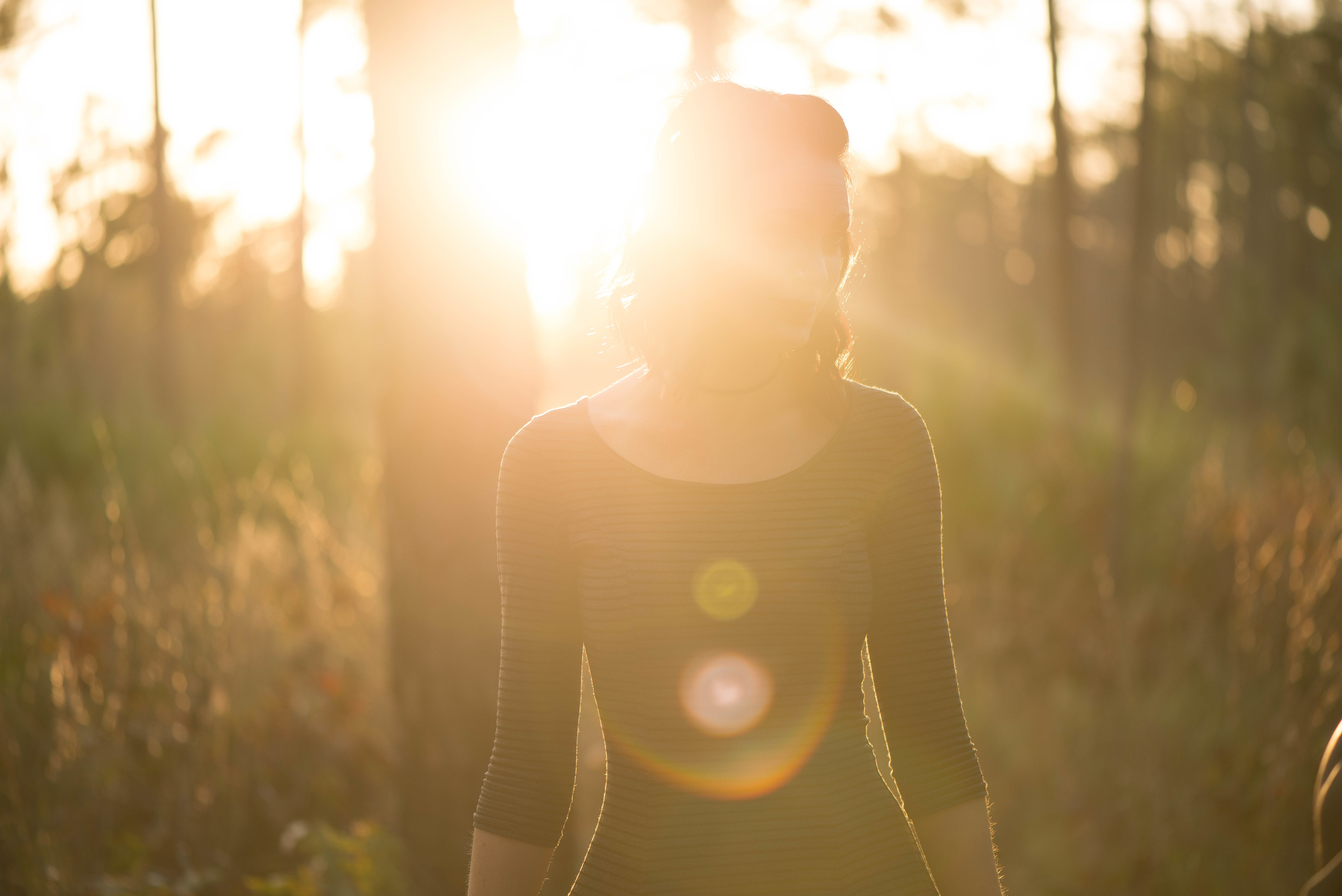 A woman standing in a forest silhouetted by the glare of a setting sun